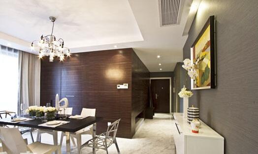 过道与餐厅的黑檀木饰面和客厅沙发背后的木地板